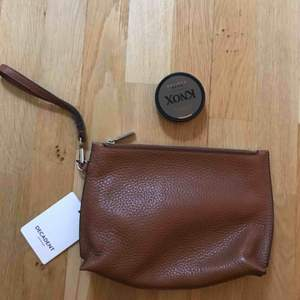 Helt oanvänd handväska från Decadent. Tjockt brunt läder med dragkedja. Nypris 1865kr