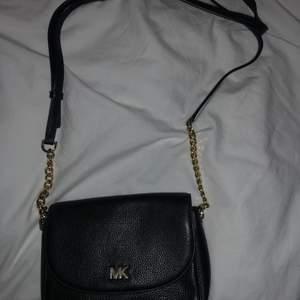 Svart Michael Kors väska med guld detaljer. Älskar denna!! Men fick en ny väska så har slutat använda den. Det går att ändra längden på axelbandet. Verkligen jättebra skick.