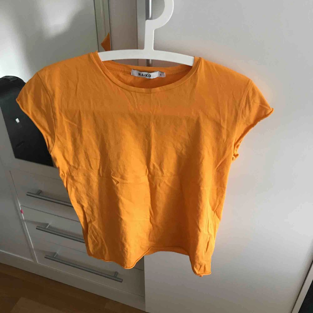 En orange t shirt från nakd, superfin passform . T-shirts.