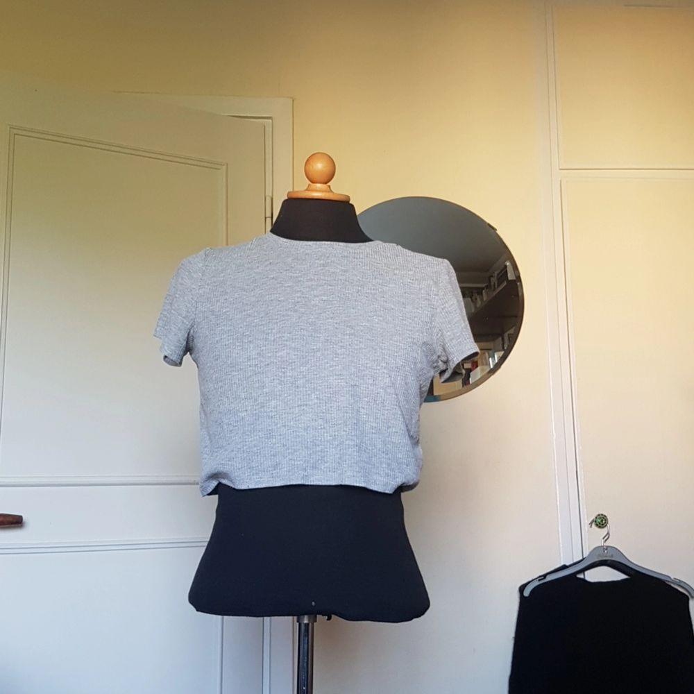 Denna gråa croptop/cropped t-shirt säljes då den inte blivit använd på flera år. Bra skick! Passar S och M. Från HM. . T-shirts.