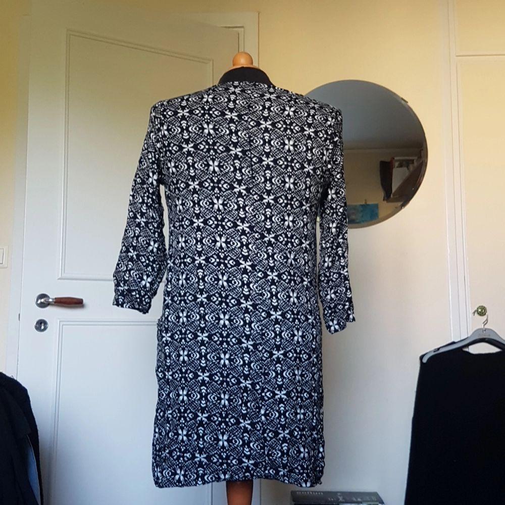 Denna superfina mönstrade klänning med fickor fram på varje sida säljes då den inte längre används. Den är rätt välanvänd och därav är en söm i ryggen lite försvagad även fast klänningen är hel. Passar S och M. Från Indiska. 3/4-ärmar.. Klänningar.