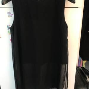 En svart ganska lång tröja med öppet på sidorna och ett svart linne under. Använd Max 2 ggr