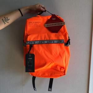 Oanvänd neon-orange backpack från Levis. 25L med laptopficka inuti.