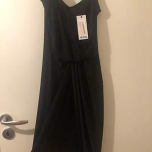 Snygg klänning från boohoo! Aldrig använd, tags kvar, sned skuren så lång på ena sidan kort på andra (se bild) skickas mot att köparen står för frakt