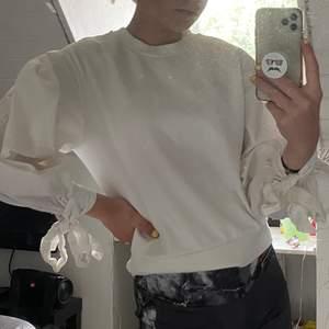 Modern sweatshirt med rosetter vid slutet av ärmen som man själv knyter. Kroppen av tröjan är vanligt tygmaterial medans ärmarna är tunnare och puffigare. Sitter snyggt och bekvämt.