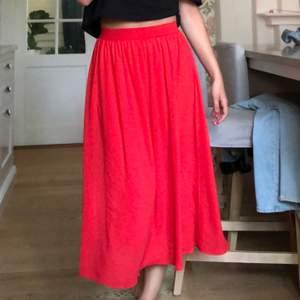 Jättefin och somrig röd långkjol som på mig (170 cm) går ned till några cm över anklarna. Materialet är tunnt och perfekt under en varm sommardag. Resorband vid midjan gör att den nog passar de flesta storlekarna! Köpare står för frakt😊