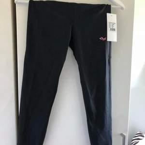 Helt nya svarta träningstights från Rönnisch med rosa bak på benen. Prislapp kvar. Skickas mot fraktkostnad 44 kr.