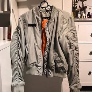 Bomberjacka i ljusblå/grå färg med orange på insidan