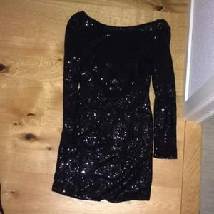 Svart glittrig klänning. Längd mellan rumpan och knäna. Aldeig använd. Öppen rygg. Köptes för 999kr