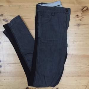 Snyggt slitna Whyred-byxor med svart resor på yttre benet.