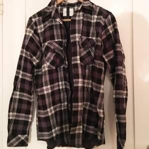 Skjorta av ganska tjock material (väldigt härlig i vintertider) med svart/vitt/grått-rutigt mönster på utsidan och svart/grått-rutigt mönster (små rutor dock) på insidan! Från Vailent