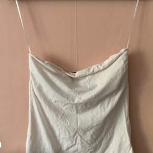 En vit tubtopp från H&M i storlek M. Toppen har en fläck som man kan se på första och andra bilden, därför säljs den för 25kr