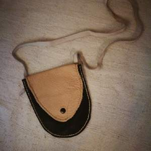 Cute little leather bag/pouch. Hand made item. The leather is rather soft to the touch and the colours are dark brown and light pink.