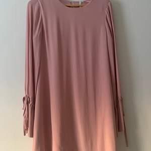 Jättefin klänning i puderrosa med knytärm vilket bildar en volang. Ej genomskinlig. Endast använd en gång. Från Nelly trend.