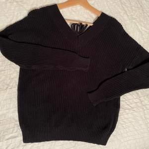 Stickad tröja med knytning där bak
