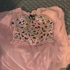 """passande balklänning i rosa/beige helt ny från nelly. kommer med extra """"diamanter"""" ifall någon ramlar av. skriv för fler bilder. nypris 799 säljer för 349. bild på paket innan betalning"""