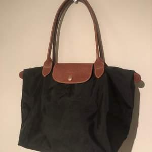 En fin Longchamp väska i svart. Väskan är i måtten 34x24 och i väldigt fint skick. Kontakta för mer information.