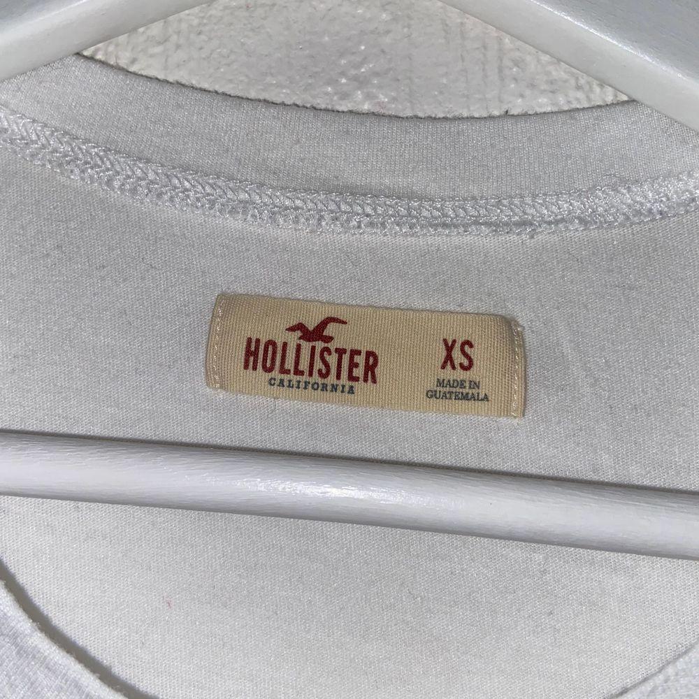 "Vit crop top med blå ""tye-dye"" logga från Hollister. Storlek XS och bra skick.. T-shirts."