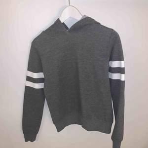 Säljer en grå hoodie med vita streck runt armarna från Gina Tricot!  Tröjan är sparsamt använd, dock har den vita färgen har spruckit lite vid armarna (se bild 3), men det är inget man tänker på! Säljer pga för liten för mig.  Frakt tillkommer🥰