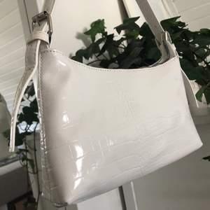 Vit väska med krokodilmönster. Väskan är helt ny, aldrig använd. Säljer pga har redan en liknande. Väskan har justerbara band. Passar perfekt att ha under armen. Ca 25cm på lång.