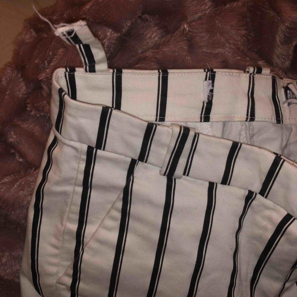 Vita kostymbyxor med svarta ränder från Berskha, inte så använda säljer pga blivit för små. Formar kroppen väldigt fin och mycket stretch. Ena bälthållaren har lossnat men går enkelt att sy, slits i änden.   Pris kan diskuteras, möts upp och fraktar🥰. Jeans & Byxor.