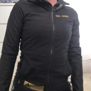"""En svart kofta från adidas med texten """"real madrid"""", gulddetaljer och Luva. Stl xs"""