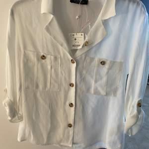 """Superfin vit skjorta som har fina """"bruna"""" knappar på. Aldrig använd då prislappen är kvar och du får med en extra knapp. Armarna kan man både ha som det är på bilden eller knäppa upp och ha som en vanlig ärm. (priset är diskutebart)"""