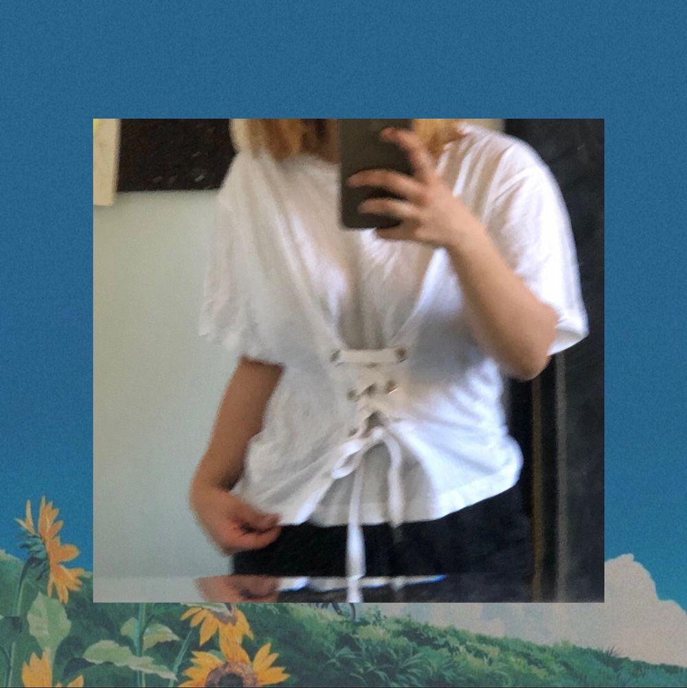 En vit korsett t-shirt den monki, ursprungspris 100kr, bra skick förutom att märkeslappen har lossnat, frakt ingår ej. T-shirts.