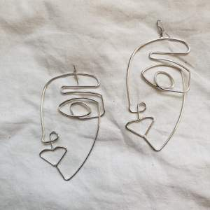 Örhängen med ansikten i ståltråd. Köpta på h&m förra året. 10 cm långa. Använda 2ggr. Frakten ingår i priset.