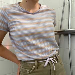 """Ljuslila randig t-shirt i storlek S. Plagget är i superfint skick och har använts max 1 gång förutom när jag provade den för att ta bilderna. Den sitter snyggt och kan både hänga rak lite """"boxy"""" eller stoppas in som på bilden! Kontakta mig för mer info🦋🦋"""