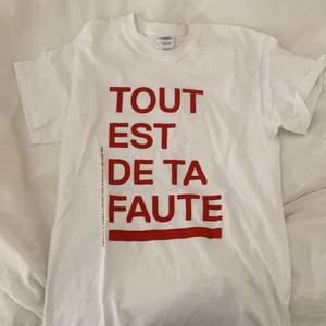 """Fin tshirt med fransk text där det står """"allt är ditt fel. Gjord av konstnären Lars Fuhre. Aldrig använd."""