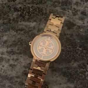 Damklocka från Tory Burch i guld med vit urtavla, mycket fint skick!!! Nypris 3500kr. Finns extra delar för att reglera storleken på armbandet som medföljer klockan.