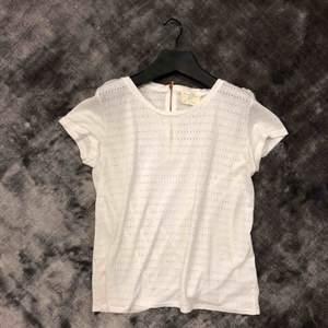 Mysig t-shirt med fina detaljer. Rose dragkedja bak på ryggen och själva t-shirten är i småhålgt typ🐚