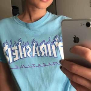 Ljusblå thrasher T-shirt med lila flammor. Mycket bra skick knappt använd