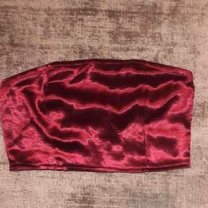 Röd glansig croptop som slutar under bysten. Använd en gång. Från nakd. Du står för frakt ca 32kr