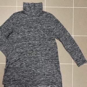 Snygg grå vit längre långärmad tröja med hög krage. Jätte skön att ha på sig. Använd ett par gånger.