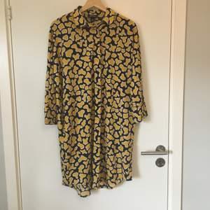 Mönstrad skjortklänning/tunika i gul,svart och vit från Monki. Stl XXS, men stor i storlek. Gott skick, knappt använd. Frakt betalas av köparen.