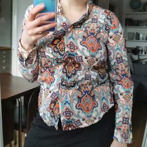 Skjorta med paisley-mönster, strl 36. Byst 92 cm, längd ca 56 cm från axeln (rundad nederkant). Jättefint skick! Köparen står för porto 63 kr (spårbart)