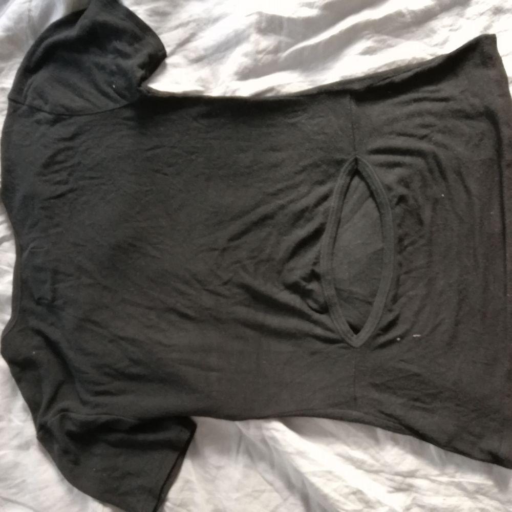 Svart t-shirt i fin kvalitet, bland annat ull. Öppning i ländryggen.          Använd men fin. Från Back . T-shirts.