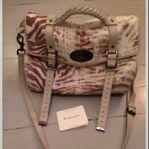 Multifärgad Mulberry-väska i modellen Alexa, Trippy Tiger Raffia Oversized Shoulder Bag. Detaljer i benvitt skinn, flätat handtag, avtagbar axelrem. Nypris ca: 8500 kr.