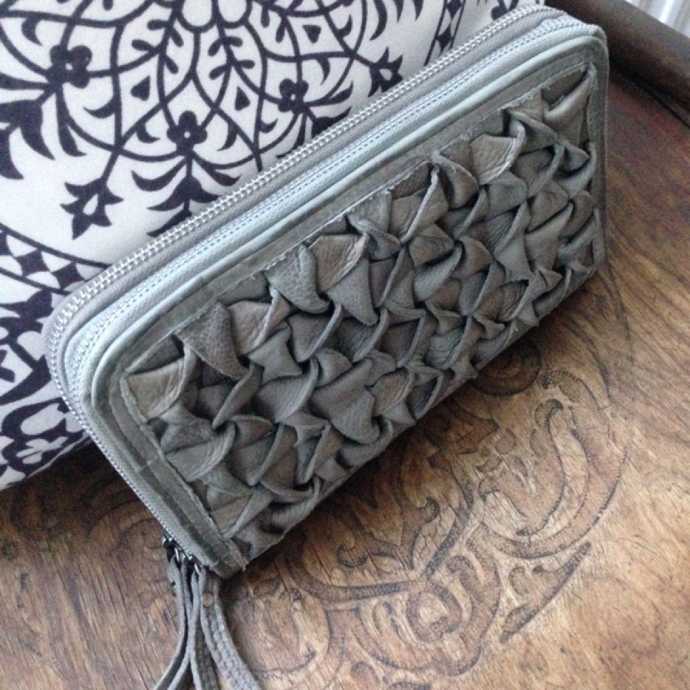 Större clutch/plånbok i grått genuint skinn med flätad framsida och två dragkedjor och flera fack inuti. Ett fack med dragkedja på baksidan. Från danska By Burin. Nypris 1299:-. Väskor.