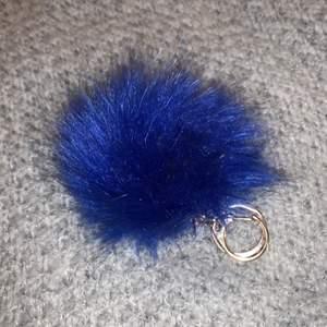 Blå fluffig boll med guld hake.