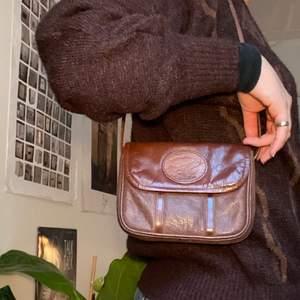Skulle gissa att det är läderimitation! Justerbart band!!! Köpt secondhand men ändå bra skick. Frakt tillkommer på 22kr