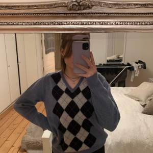 En blå tröja med rutigt mönster i färger marinblå och vit, v ringad hals och helt blå där bak, säljer pga att jag inte använder den längre, köpte den från en använde på plick för några månader sen