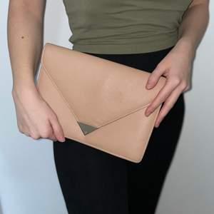 Beige kuvertväska som även har band i guld färg! Kan användas både på armen och i handen beroende på tillfälle. Från märket Mango. Köparen står för frakt! 💙