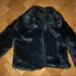Skön kort svart/grå päls jacka köpt nu i november och använd ändast 3/2gånger så den är i perfekt skick Storlek 38/36 ny pris 999kr mitt pris 450kr & frakten ingår o priset🌸