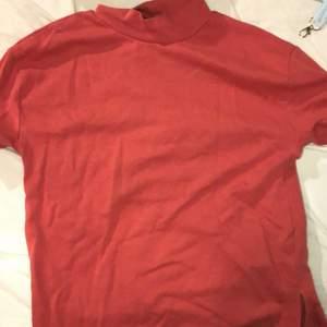 Rosa T-shirt i lite tjockare material med slits nedtill på båda sidorna.