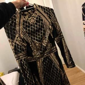 Svart knälång klänning med guldiga paljetter, storlek 34. Aldrig använd, bara hängt på klädstången.