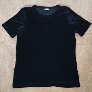 Svart T-shirt från Cubus i 95% polyester och 5% elastan. Materialet känns som sammet. På båda sidorna är det en liten slits. Använd en gång.  Kan mötas upp alt. skicka.