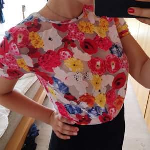 T-shirt från Monki i semi-transparent tyg med blommigt tryck i bjärta färger.